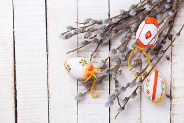 Decorative Eeaster eggs and willow branches on wooden background