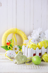 Colorful Easter eggs and rabbit  on white  wooden background.