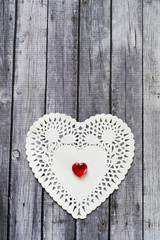 white doily with ruby heart in center on wood background