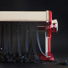 Squid ink tagliatelle being cutted with pasta machine
