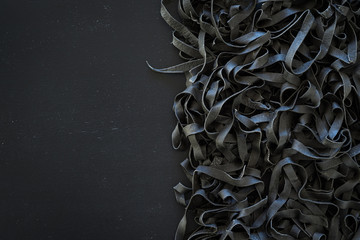 Homemade uncooked black squid ink tagliatelle on black background