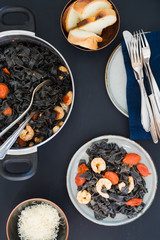 Homemade black squid ink tagliatelle with tomatoes and shrimps sauce