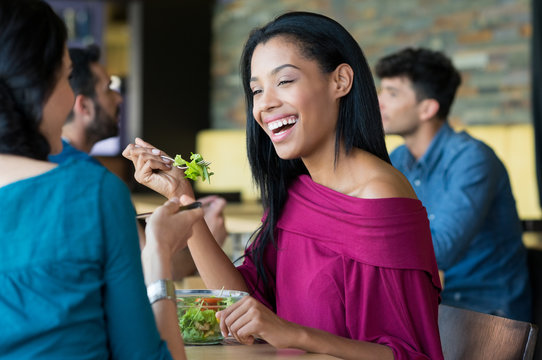 Young beautiful woman eating salad