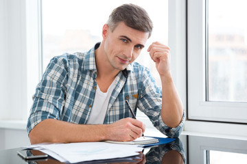 Handsome man sitting at the table and writing