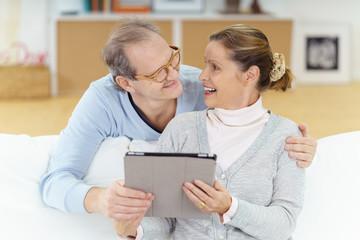 lachendes ehepaar mit tablet-pc