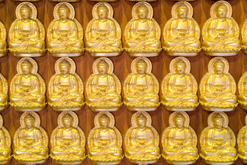 Golden Buddha line up along the wall of chinese temple