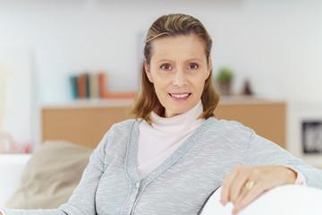 attraktive ältere frau sitzt zuhause auf dem sofa