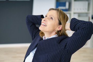 ältere geschäftsfrau lehnt sich zufrieden zurück