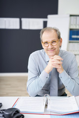 kompetenter geschäftsmann sitzt am schreibtisch in seinem büro