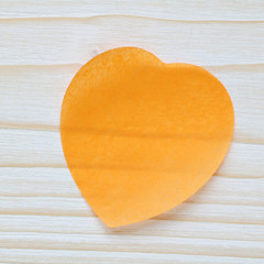 Cœur en papier orange sur fond bois blanc