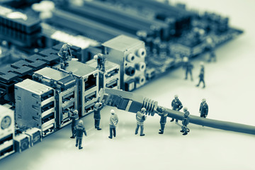 Technicians connecting network cable to motherboard.