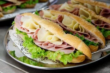 Yellow sliced cheese, ham and salad white  baguettes on doily and stainless steel tray.