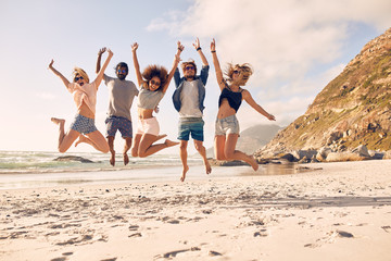 Group of friends on the beach having fun Wall mural
