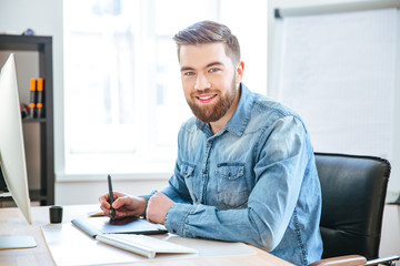 Happy designer working using pen tablet with stylus in office