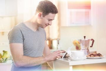 Mann informiert sich morgens beim Kaffee mit Tablet online