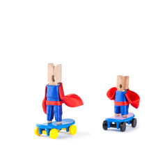 Old and youth clothespin skateboarders. Team sport concept. Skating superheroes. Hero in blue, red suits on blue skate board. White background, copy space
