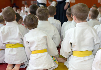 Foto op Aluminium Vechtsport Children in kimono sitting on tatami on martial arts seminar