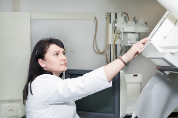 Brunette female doctor working with x-ray machine
