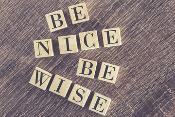 Be Nice Be Wise message formed with wooden blocks