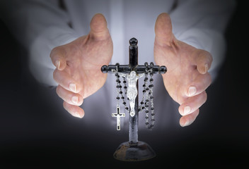 Man's hands with crucifix and a black rosary