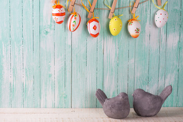 Two decorative birds and colorful easter eggs on rope on wooden