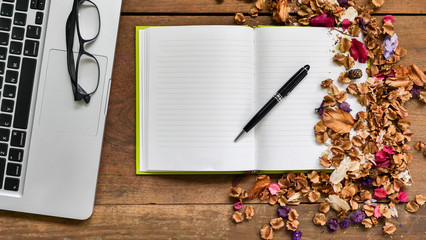 Top view workspace with notebook,pen,glasses,laptop and dried flowers on wooden table background .