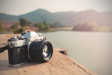 Vintage camera with view of lake and mountain Wall mural