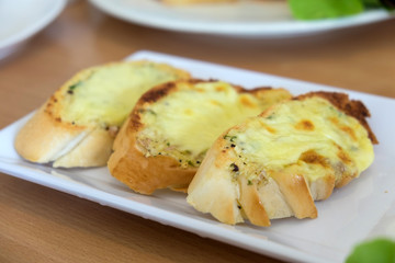 Close-up of a dish of garlic bread with cheese