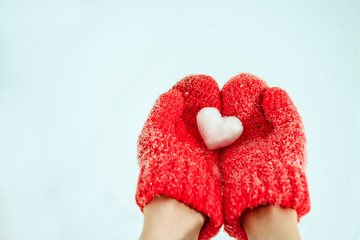 Female hands in warm red crocheted mittens with snowy heart. Whi