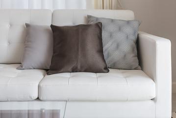 modern white sofa with brown pillows