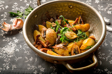 Fried potatoes with mushrooms and onions at home in a frying pan