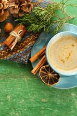 Cup of coffee with sweet spices on napkin on green wooden background