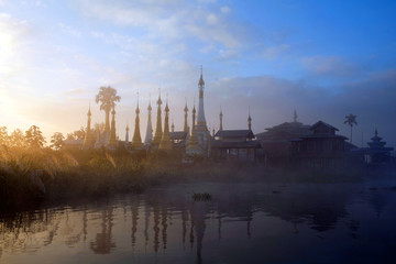 Ancient pagoda and monastery over mist on Inle lake, Myanmar