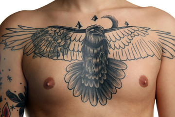 Bird tattoo on male chest over white background