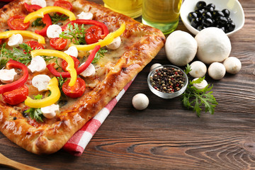 Freshly homemade pizza on wooden background