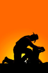 silhouette of cowboy kneel and lean on saddle