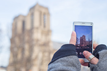 Paris sightseeing. Girl making a photo of Notre Dame