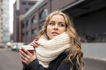 Teenage woman holding a cup of hot drink outdoors