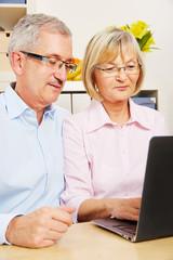 Paar Senioren am Laptop Computer zu Hause