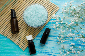 bottles essential oil and sea salt herbal bath  on wooden table, Spa with flowers