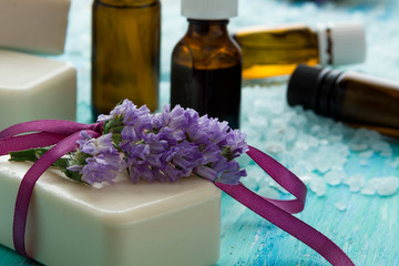 natural organic soap bottles essential oil and sea salt   on a blue wooden table, with flowers