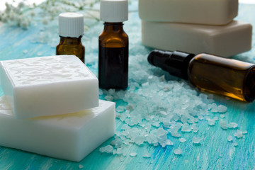 natural organic soap bottles essential oil and sea salt   on a blue wooden table, Spa
