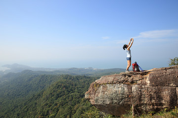 young woman backpacker taking photo with smartphone on mountain peak