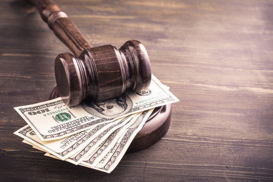 Gavel and dollars banknotes on table