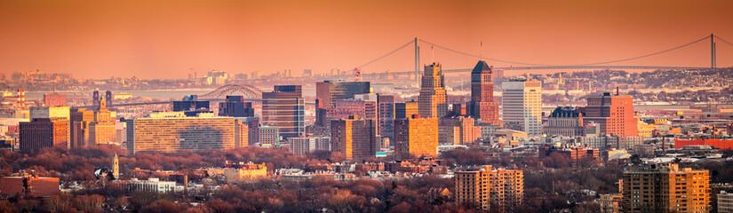 Newark New Jersey skyline viewed from Eagle Rock reservation under an orange sunset. In the background, under a hazy sky, Verrazano bridge links Staten Island to Brooklyn.