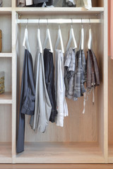 modern closet with row of pants hanging in wooden wardrobe