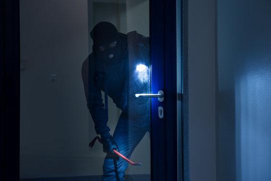 Thief With Flashlight Trying To Break Door