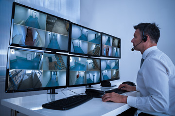 Security System Operator Looking At CCTV Footage At Desk