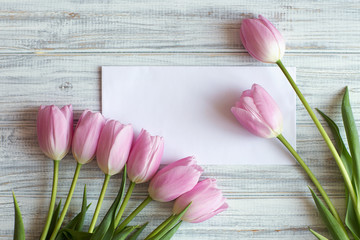 bouquet of pink tulips lie on textural table, next to a white envelope