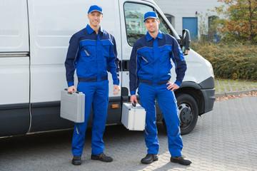 Confident Technicians Standing Against Truck